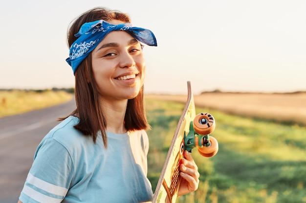 Buiten schot van jonge volwassen innemende vrouw die een blauw casual stijl t-shirt en haarband draagt, staande met longboard in handen, camera kijkend met een charmante glimlach.