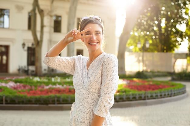 Buiten schot van jonge vrolijke brunette vrouw in witte polka-dot jurk breed glimlachend en hand opsteken met overwinning gebaar, staande boven de stedelijke omgeving