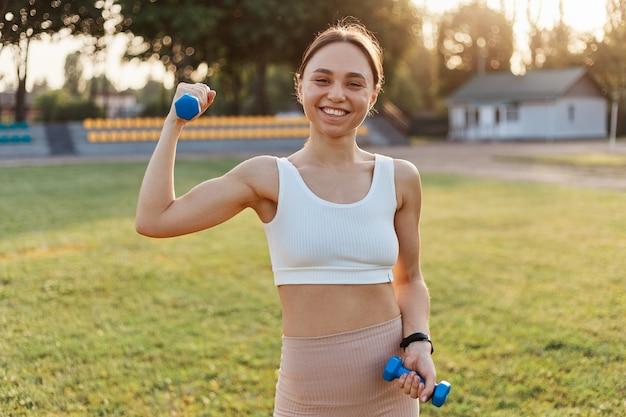 Buiten schot van jonge vrouwelijke atleet met halters die zich uitstrekken en opwarmen in het stadion, glimlachend naar de camera kijkend, geluk, sport en fitness uitdrukkend.