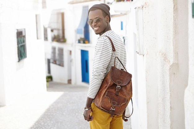 Buiten schot van knappe gelukkig jonge afro-amerikaanse mannelijke reiziger met lederen rugzak staande op betonnen muur op smalle straat terwijl sightseeing in vakantieoord tijdens zijn zomervakantie