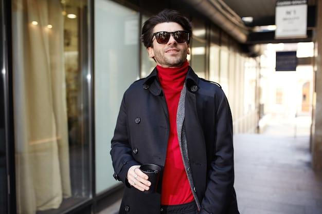 Buiten schot van knappe jonge bebaarde brunette man koffie drinken tijdens het lopen naar zijn werk en frisse lucht inademen, geïsoleerd over stedelijke achtergrond