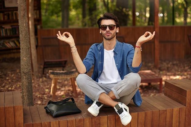 Buiten schot van knappe jonge bebaarde man zit over openbare groene tuin met kalm gezicht, mediteren met gekruiste benen en opgeheven handen in mudra teken