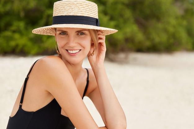 Buiten schot van knappe vrouw met glanzende aangename glimlach, heeft een gezonde, zuivere huid, baadt in de zon op het strand, draagt zomerkleding, heeft een vrolijke uitdrukking. mooie vrouw alleen aan de kust