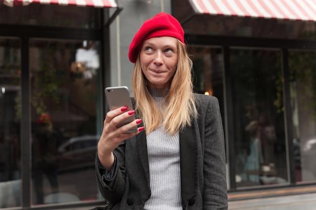 Buiten schot van mooie jonge blonde langharige vrouw in elegante kleding mobiele telefoon in opgeheven hand houden en dromerig naar boven kijken, onderlip bijten