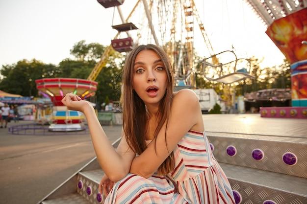 Buiten schot van mooie jonge vrouw met bruin haar in lichte zomerjurk op zoek met verbaasd gezicht, zittend op de trap met handen op haar knieën, samentrekkende voorhoofd met brede mond geopend