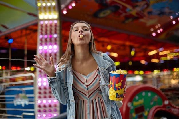 Buiten schot van mooie jonge vrouw met bruin haar plezier maken over pretpark, popcorn in haar mond stoppen en kijken met opgeheven hand, vrijetijdskleding dragen