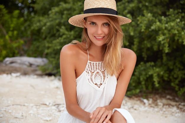 Buiten schot van mooie vrouw heeft een positieve uitstraling, draagt zomerhoed en jurk, vormt alleen op zandstrand, heeft goede rust. aantrekkelijke jonge vrouw met gebruinde huid recreëert tijdens de zomertijd