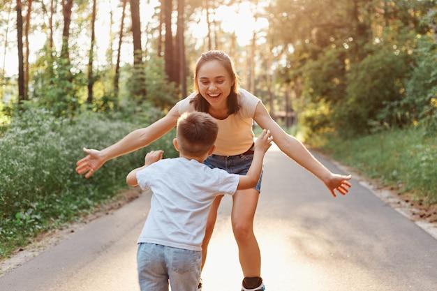 Buiten schot van mooie vrouw met brede glimlach en positieve gelukkige uitdrukking die haar zoon met gespreide armen vangt terwijl ze samen skaten in het zomerpark, actieve gezonde levensstijl.