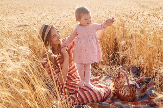 Buiten schot van mooie vrouw met haar dochtertje peuter dragen roze jurk en panty in tarweveld op zomerdag, mama gekleed gestreepte jurk en strooien hoed poseren omringd met aartjes.