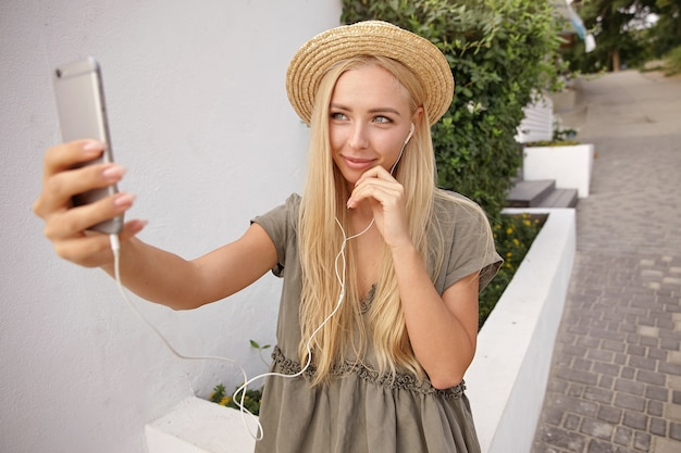 Buiten schot van schattige blonde vrouw in strooien hoed met koptelefoon in oren, zelfportret maken met haar smartphone, teder en romantisch kijken
