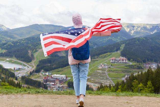 Buiten schot van slank meisje op de natuur met amerikaanse vlag op haar schouders, vrouw draagt casual roze jas, broek