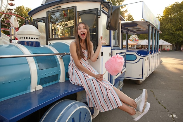 Buiten schot van vrolijke aantrekkelijke dame in lichte lange jurk zittend op stoomtrein in pretpark op warme zomerdag, poseren met brede mond geopend en roze suikerspin in de hand