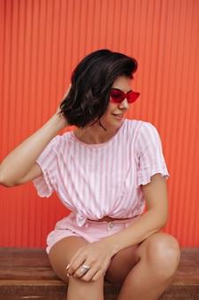 Buiten schot van vrouw in roze gestreepte t-shirt. brunette vrouw in zonnebril poseren op houten bank.