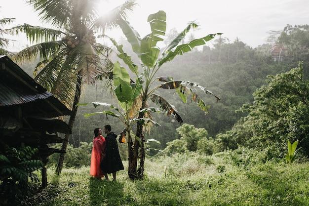 Buiten schot van vrouwelijke toerist in roze regenjas poseren met vriendje op jungle. portret van paar koelen in tropisch woud.