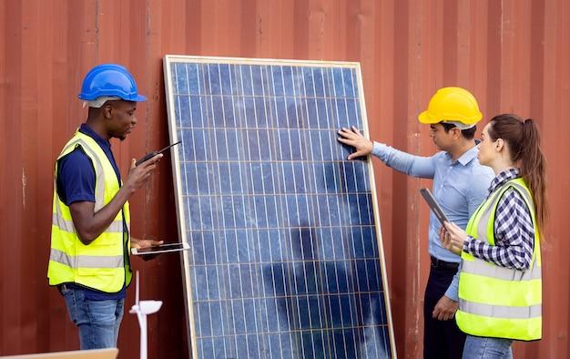 Buiten schot van zwarte afrikaanse ingenieur inspecteren elektrische zonnepaneel dragen veiligheidshelm, beschermende lenzenvloeistof en veiligheidsuitrusting,