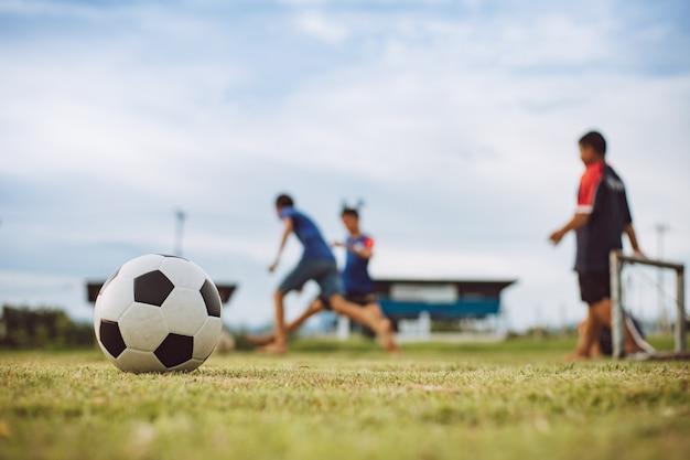 Buiten sporten van een groep kinderen die plezier hebben met voetballen om te oefenen