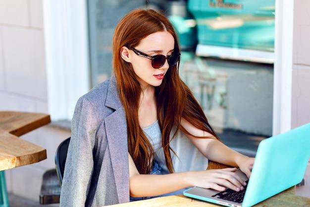 Buiten stad mode portret van jonge zakenvrouw werken in café op terras op zonnige dag, casual stijlvolle outfit, mint details, met behulp van haar laptop, cafépauze, bedrijfsconcept.