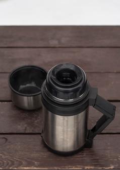 Buiten thermoskan met koffie op een bankje in de winter bovenaanzicht.