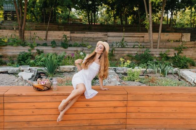 Buiten van dromerige blootsvoets dame met lang krullend haar zittend op een houten bankje in het park en wegkijken. romantisch meisje in strooien hoed en witte jurk poseren voor bloembed.