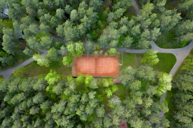 Buiten verlaten tennisbanen voor tennis tussen het bos in het park.