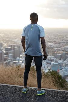Buiten verticale shot van atletische man draagt sportkleding, staat achterover, bewondert uitzicht op de natuur en stadsgezicht van bovenaf, draagt sportfles met water, geniet van ochtendtraining. fitness concept