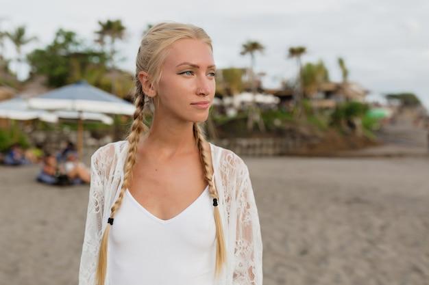 Buiten vrouwelijk profiel portret inademen van frisse lucht op het strand met de oceaan op de achtergrond. vrij kaukasisch meisje dat in de ochtend op de oceaan loopt