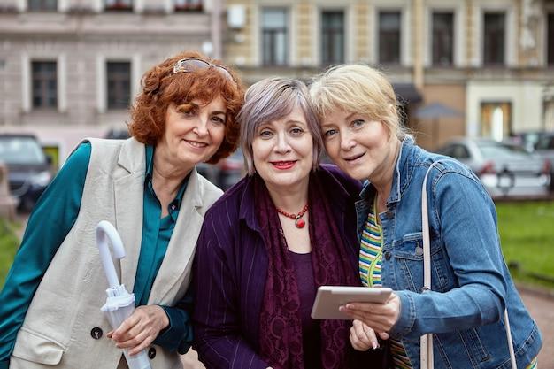 Buiten worden drie oudere blanke dames gefotografeerd.