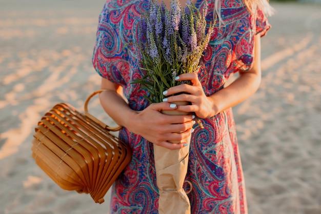 Buiten zomer beeld van mooie romantische blonde vrouw in kleurrijke jurk wandelen op het strand met boeket lavendel.