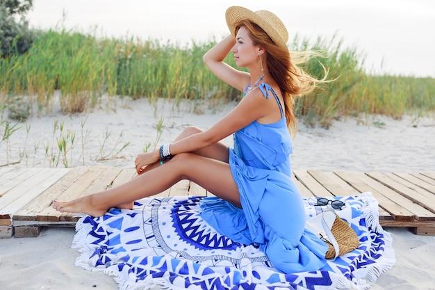 Buiten zomer beeld van romantische vrouw in strooien hoed ontspannen op zonnig strand in blauwe jurk.