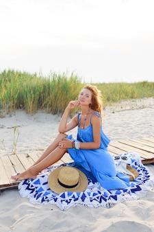 Buiten zomer beeld van romantische vrouw ontspannen op zonnig strand in blauwe jurk.