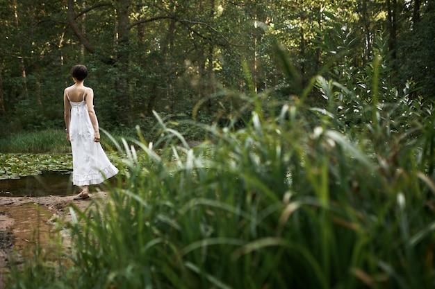 Buiten zomer foto van romantische schattige jonge vrouw, gekleed in lange witte jurk ontspannen in de wilde natuur alleen in het weekend, staande bij de vijver op de achtergrond met vers groen gras op de voorgrond