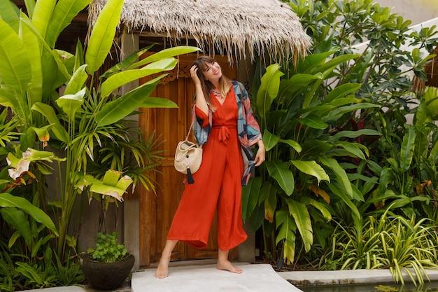 Buiten zomer mode foto van prachtige vrouw in boho outfit poseren in tropische luxeresort. volledige lengte. tropische planten.