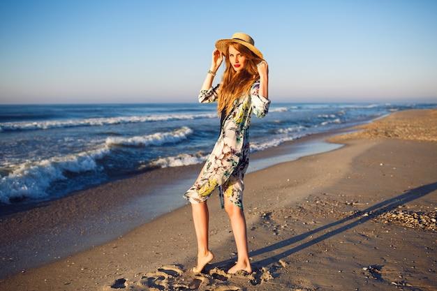 Buiten zomer mode portret van blonde model poseren in de buurt van de oceaan op eenzaam strand, getinte kleuren, ontspannende luxevakantie