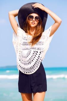 Buiten zomer mode portret van mooie elegante vrouw met perfect lichaam en lange benen dragen hoed en boho chique outfit, poseren op winderige zonnige dag op tropisch strand, geweldig uitzicht op de oceaan