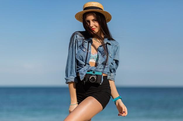 Buiten zomer mode portret van prachtige vrouw met bruin lichaam, volle rode lippen en lange sterke benen die zich voordeed op het tropische zonnige strand.