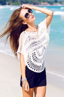 Buiten zomer mode portret van sexy vrouw in stijlvolle boho chick outfit en zonnebril poseren op tropisch strand, geweldig uitzicht op de helderblauwe oceaan
