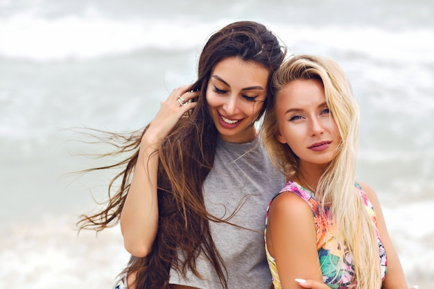 Buiten zomer mode portret van twee mooie beste duivels meisjes, poseren in de buurt van de oceaan, winderig bewolkt weer.