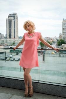 Buiten zomer mode prachtig portret van mooie jonge blonde sexy vrouw, gekleed in korte roze jurk poseren in de straat.