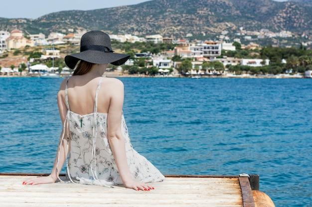 Buiten zomer portret van jonge mooie vrouw kijken naar de zee in de haven van agios nikolaos, geniet van haar vrijheid en frisse lucht, gekleed in stijlvolle hoed en kleding.
