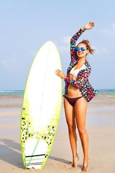 Buiten zomer portret van lachende vrouw met surfer board in de buurt van blauwe oceaan