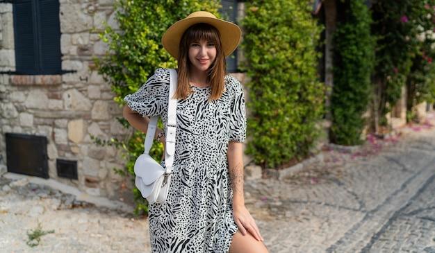 Buiten zomer portret van mooie vrouw wolking in oude europese stad. het dragen van een strooien hoed.