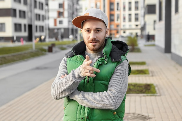 Buiten zomer shot van trendy jonge bebaarde man in stijlvolle snapback poseren in stad met moderne gebouwen met meerdere verdiepingen in wijsvinger, glimlachen, kiezen