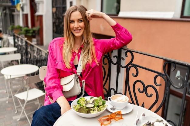 Buiten zomerportret van vrolijke blonde vrouw die geniet van haar smakelijke brunch in café met terras in de stad.