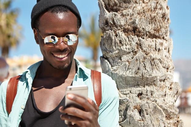 Buiten zomerportret van vrolijke donkere man in trendy kleding met behulp van mobiele telefoon, genietend van online communicatie met vrienden via sociale netwerken, berichten, foto's verzenden tijdens reis naar het buitenland