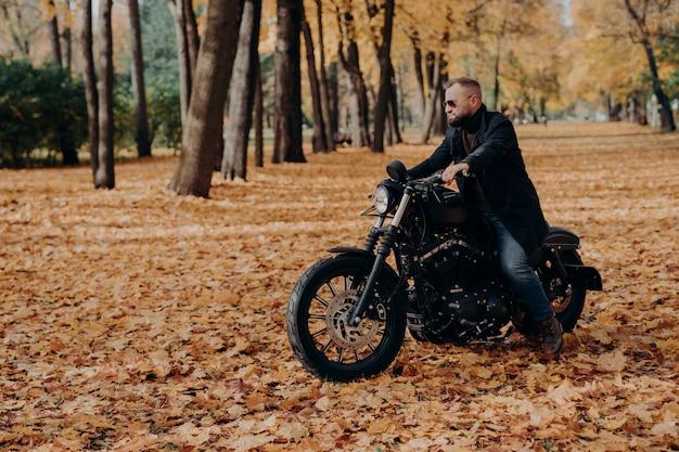 Buitenaanzicht van actieve mannelijke motorrijder rijdt fiets, draagt trendy zonnebril en zwarte jas