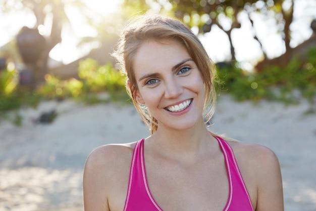 Buitenaanzicht van gelukkige mooie jonge vrouwelijke fitnesstrainer bereidt zich voor op masterclass en betrokken bij actieve training, gaat graag sporten voor meer vitaliteit en flexibiliteit. actieve levensstijl