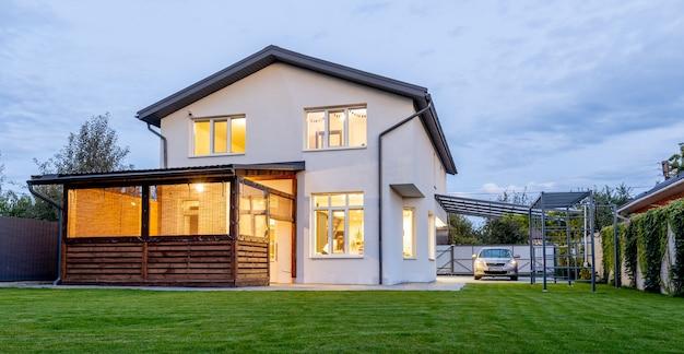 Buitenaanzicht van modern wit huis met binnenplaats, patio, groen grasgazon, tuin en een auto in de avond