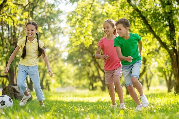 Buitenactiviteiten. twee lachende schattige junior meisjes en vrolijke jongen die bal samen achtervolgen op gras in park