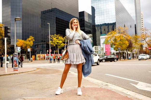 Buitenbeeld van de volledige lengte van stijlvolle vrouw spreken door haar smartphone, poseren in de buurt van modern zakencentrum, hipster casual stijlvolle look, lente herfst middenseizoen.