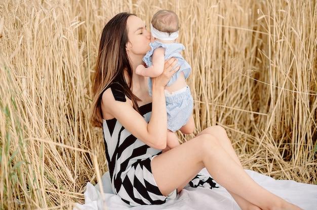 Buitenbeeld van een liefdevolle zorgzame vrouw in een gestreepte jurk die haar dochtertje kust, tegen de achtergrond van een tarweveld.